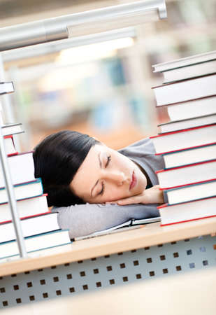 Female student sleeping at the desk with piles of books. Tired of training photo