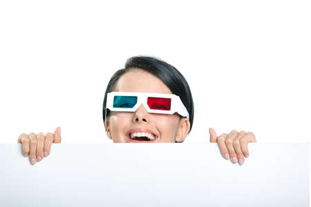 Girl in 3D spectacles peeps out from behind the copyspace, isolated on white photo