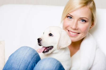 animal woman: Close up of woman in white sweater with white puppy sitting on her knees Stock Photo
