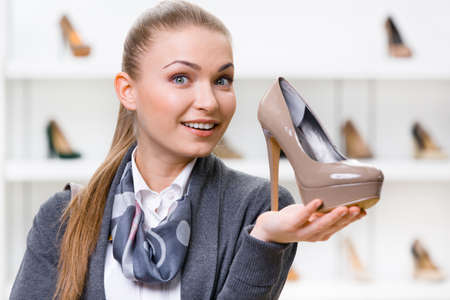 formats: Portrait of woman keeping coffee-colored shoe in shopping center against the showcase with pumps