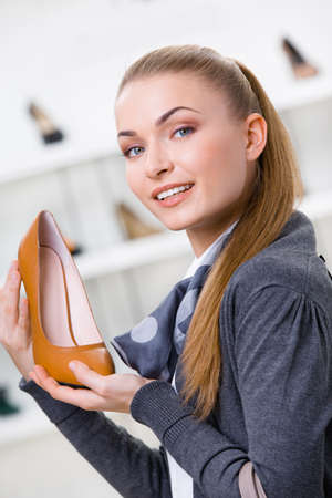 bargain: Portrait of woman keeping brown leather shoe in shopping center against the showcase with shoes