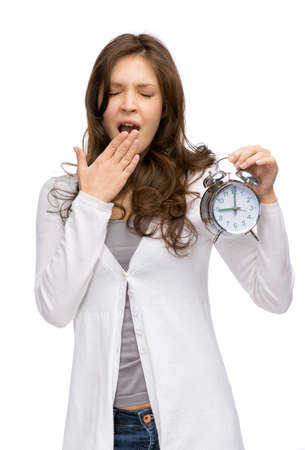 Half-length portrait of yawning woman keeping alarm clock, isolated on white photo