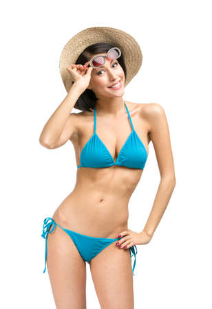 Portrait of lady wearing bikini, hat and sunglasses, isolated on white. Concept of summer holidays and traveling photo