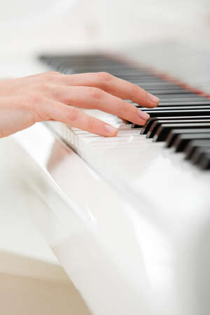 Close up of hand playing piano. Concept of music and art photo
