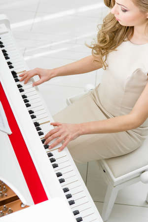Top view of woman playing piano. Concept of music and arts photo