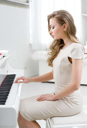 side keys: Profile of woman wearing beige dress and playing piano. Concept of music and art