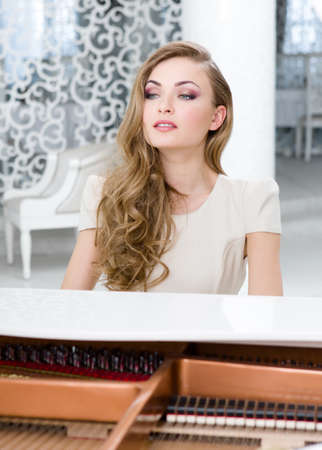 Portrait of woman sitting and playing piano. Concept of music and entertainment Stock Photo - 24480344