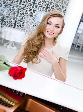 Portrait of woman with claret rose playing piano. Concept of music and leisure Stock Photo - 24480359