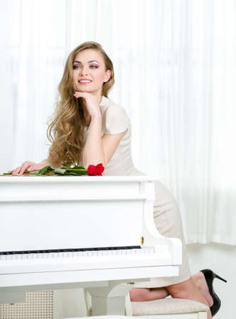 Portrait of woman in beige dress propping head and standing near the piano with red rose on it. Concept of music and arts Stock Photo - 24480361