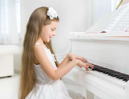 어린 소녀: 하얀 드레스를 연주 피아노에 어린 소녀의 프로필입니다. 음악 공부와 예술의 개념 스톡 사진