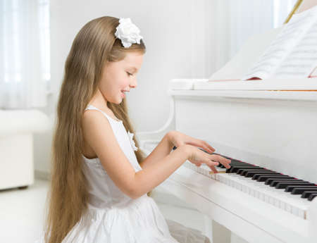 piano player: Profile of little girl in white dress playing piano. Concept of music study and art