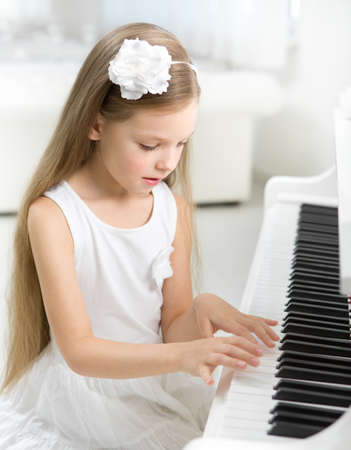 Portrait of little girl in white dress playing piano. Concept of music study and arts photo