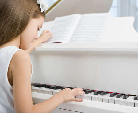 Side view of little girl in white dress playing piano. Concept of music study and arts Stock Photo - 24480369