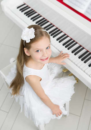 Top view of little girl in white dress playing piano. Concept of music study and creative hobby Stock Photo - 24480370