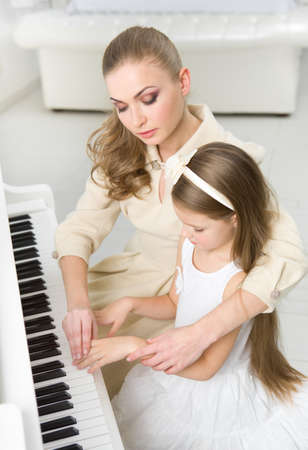 teaches: Tutor teaches little girl to play piano. Concept of music study and leisure