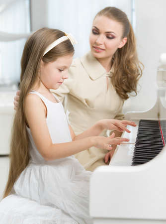 teaches: Master teaches little girl to play piano. Concept of music study and arts