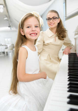 Master teaches little girl to play piano. Concept of music study and art Stock Photo - 24480379