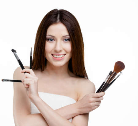 Woman handing a set of cosmetic brushes for make-up, isolated on white photo