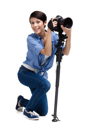Lady takes pictures holding photographic camera, isolated on white Stock Photo - 24480510