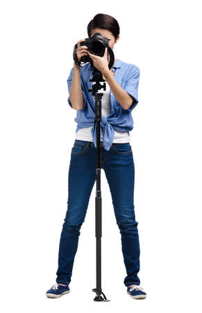 Woman takes snapshots holding photographic camera with monopod, isolated on white Stock Photo - 24480513