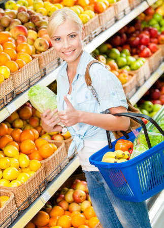 Girl at the market choosing fruits and vegetables hands cabbage and full of purchases hand cart and thumbs up photo