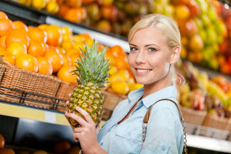 Girl at the market choosing fruits and vegetables hands pineapple photo