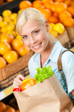 Girl hands paper bag with fresh vegetables against the shelves of fruits in the shopping center photo