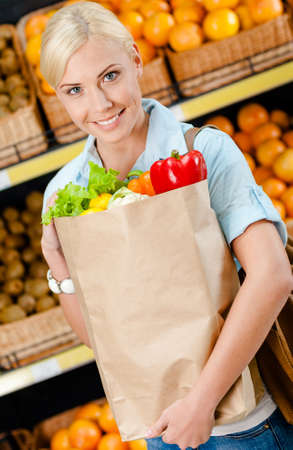 Girl hands bag with fresh vegetables against the shelves of fruits in the shopping mall photo