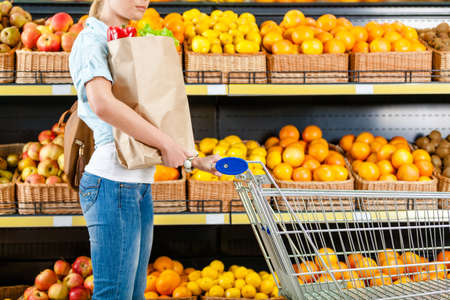 Girl with cart hands bag with fresh vegetables against the shelves of fruits in the shop photo