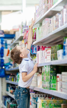 reach customers: Little boy chooses cosmetics on the shelves of the market