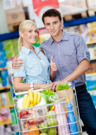 Half-length portrait of couple in the market with cart full of food. Concept of consumerism and healthy food photo