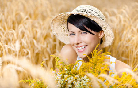 non urban: Pretty girl in straw hat and white T-shirt against rye field hands flowers Stock Photo