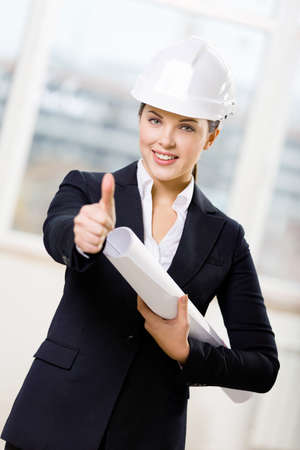 Wearing white hand hat female engineer with blueprint thumbs up photo