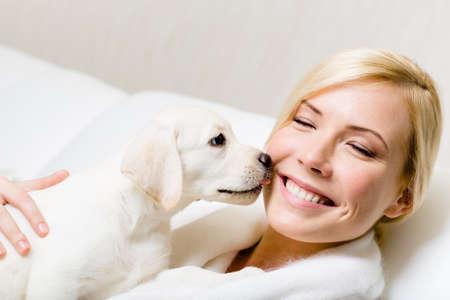 Puppy van Labrador likt het gezicht van de vrouw, zittend op de witte lederen sofa