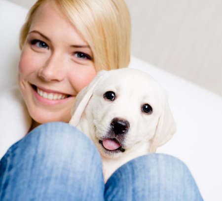 knees up: Close up of woman in white sweater with puppy sitting on her knees Stock Photo