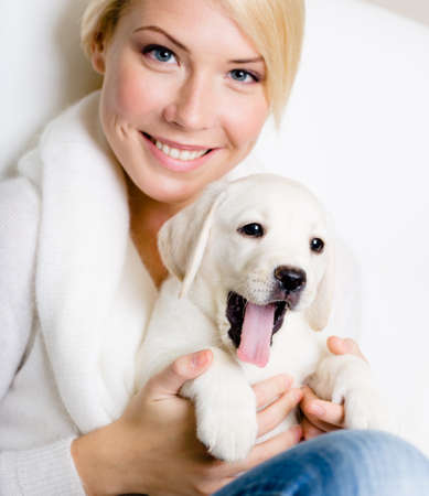 Close up of woman in white sweater with white Labrador puppy sitting on her knees and yawning photo