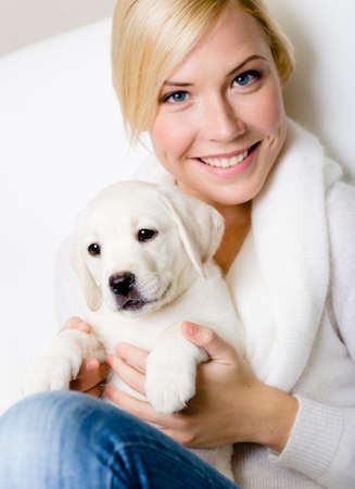 Close up of woman in white sweater with white Labrador puppy sitting on her knees photo