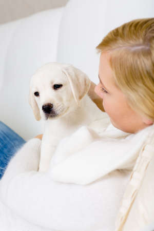 Close up of woman in white sweater embracing white white puppy photo