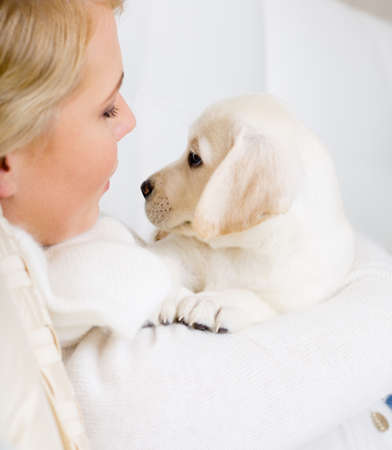 Close up of woman in white sweater embracing white labrador puppy photo