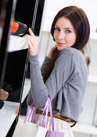 bargain: Woman choosing a pair of footwear in shopping center Stock Photo