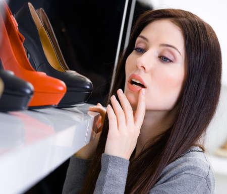 comprando zapatos: Cerca de la mujer de elegir un par de zapatos en el centro comercial