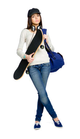 Full-length portrait of teenager with skateboard wearing peaked cap, earphones and rucksack, isolated on white. Concept of young generation Stock Photo - 24480827
