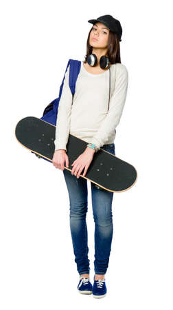 Full-length portrait of teenager with skateboard wearing peaked cap, headphones and rucksack, isolated on white. Concept of young generation Stock Photo - 24480828