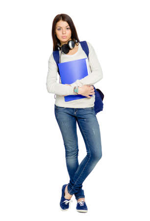 Full-length portrait of teenager with folder, rucksack and earphones, isolated on white photo