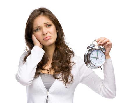 joyless: Half-length portrait of tired woman handing alarm clock, isolated on white