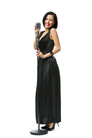 Full-length portrait of woman singer wearing long black evening dress and holding microphone photo