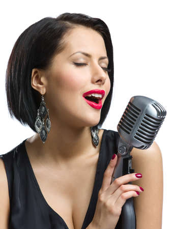 Portrait of female singer with closed eyes wearing black evening dress and keeping microphone, isolated on white. Concept of music and retro fashion photo