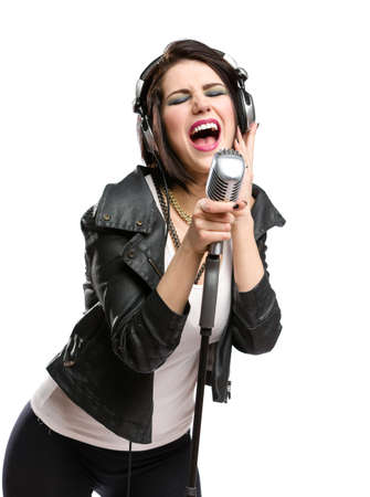 Half-length portrait of rock singer with earphones wearing leather jacket and keeping static microphone, isolated on white. Concept of rock music and rave Stock Photo