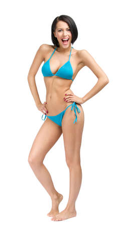 Full-length portrait of pretty female wearing blue bikini, isolated on white. Concept of summer holidays and traveling photo