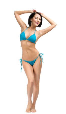 Full-length portrait of young girl wearing blue bikini, isolated on white. Concept of summer holidays and traveling photo